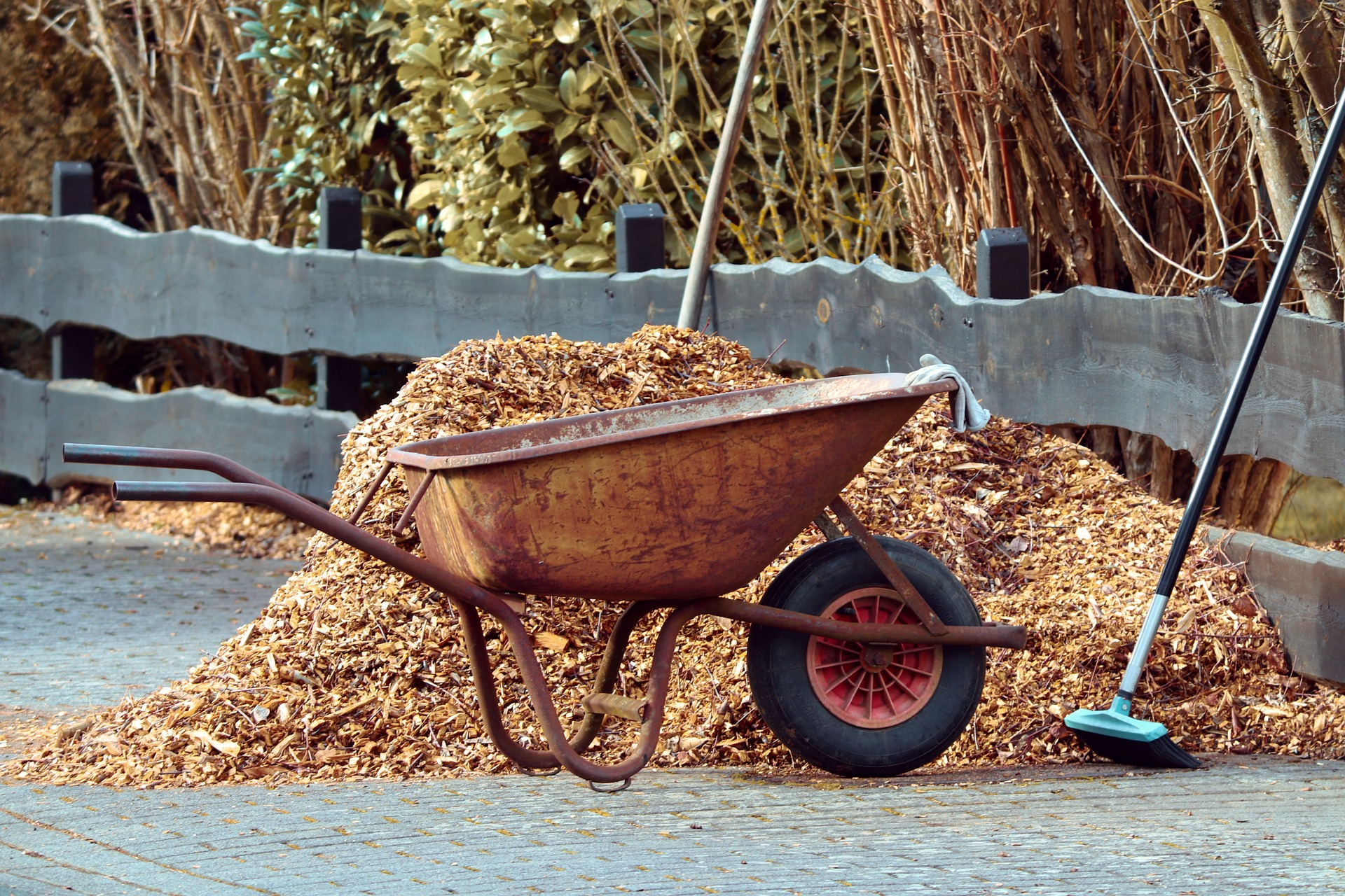 wood mulch advantages, wheelbarrow hauling brown mulch
